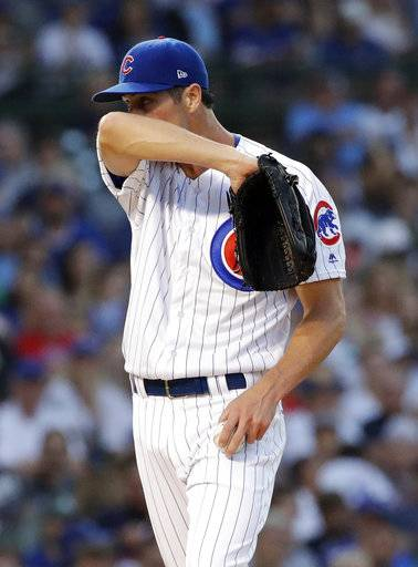 Chicago Cubs starting pitcher Cole Hamels wipes his face during the second inning of a baseball game against the Washington Nationals, Sunday, Aug. 12, 2018, in Chicago.