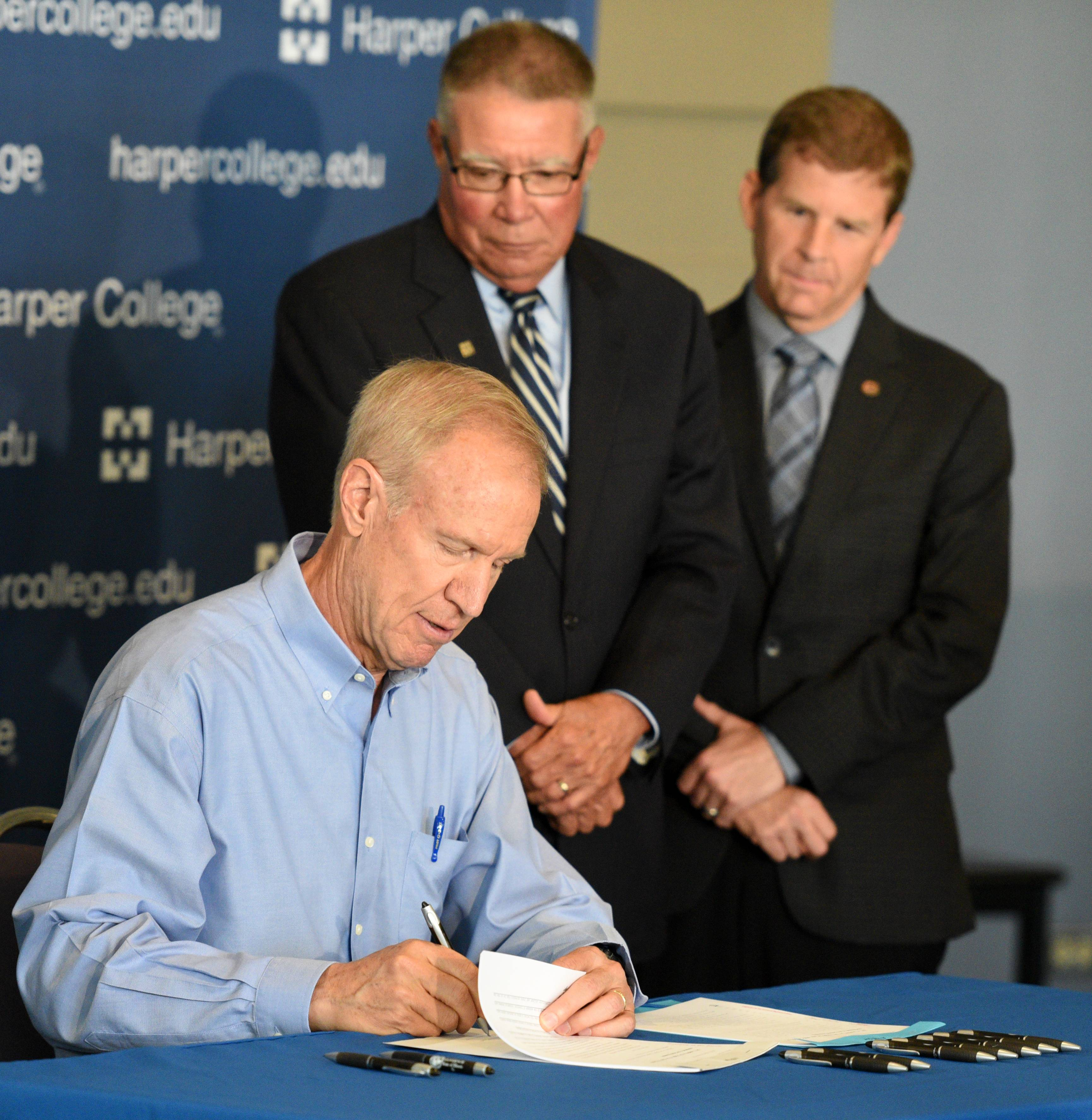 Gov. Bruce Rauner signs a pair of higher education bills Monday at Harper College in Palatine as Harper President Ken Ender, center, and Republican state Sen. Tom Rooney of Rolling Meadows watch.