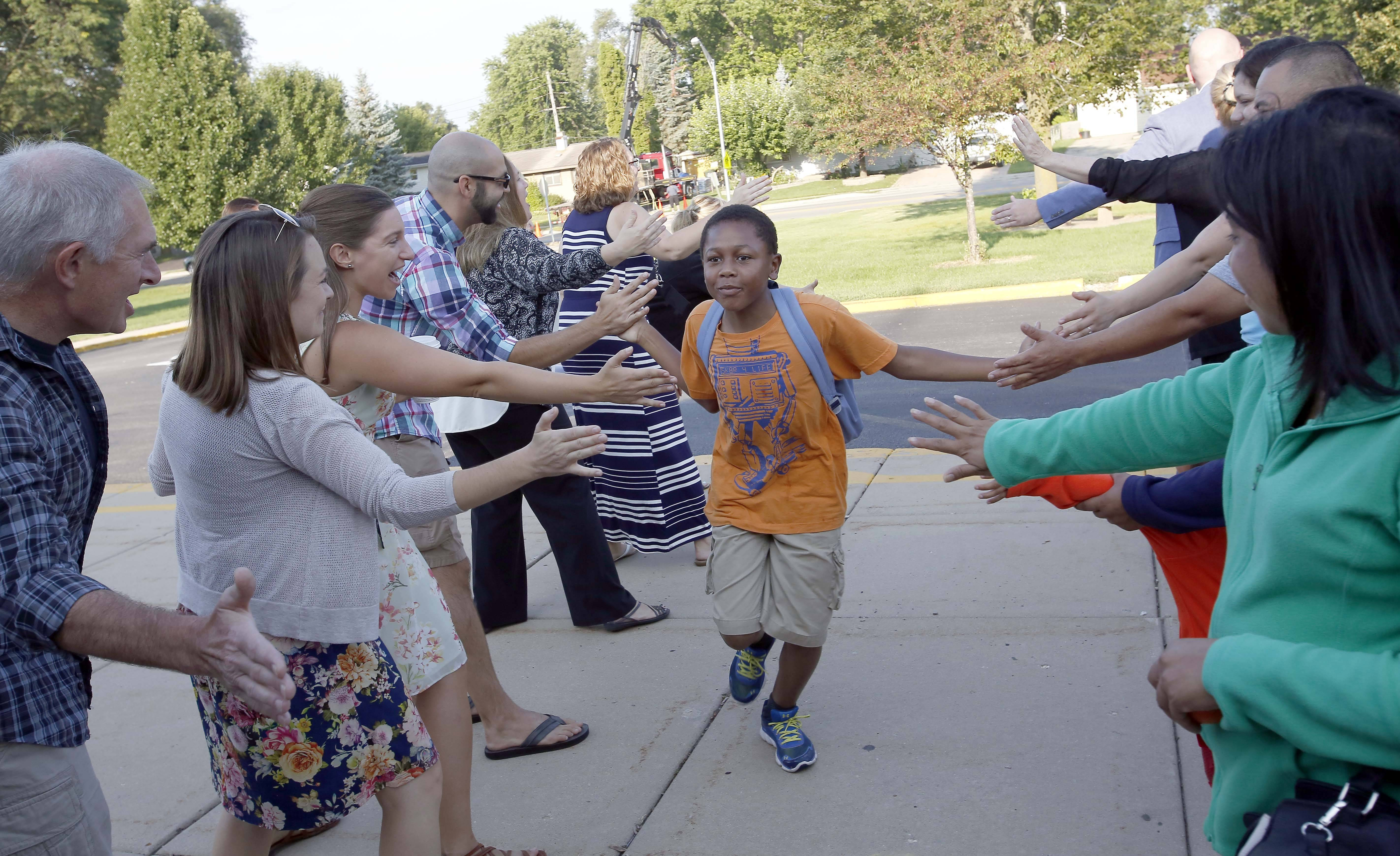 Ten-year-old Dominick Roman runs down the line of high-fives on his way to school Tuesday during the first day of classes at Golfview Elementary School in Carpentersville.