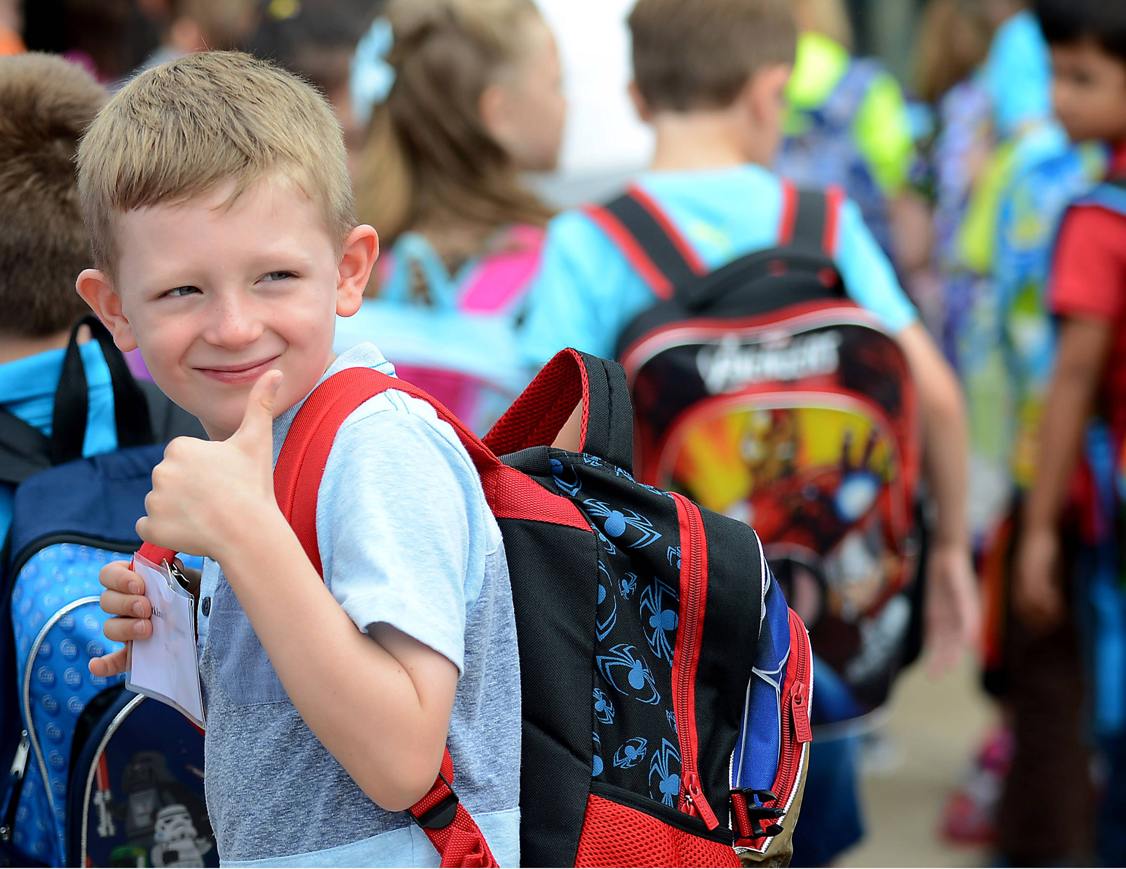 Jack Atkins gives a quick look back and thumbs-up to his parents before filing in for his first day of kindergarten at Prairie View Elementary School in Elgin Wednesday.