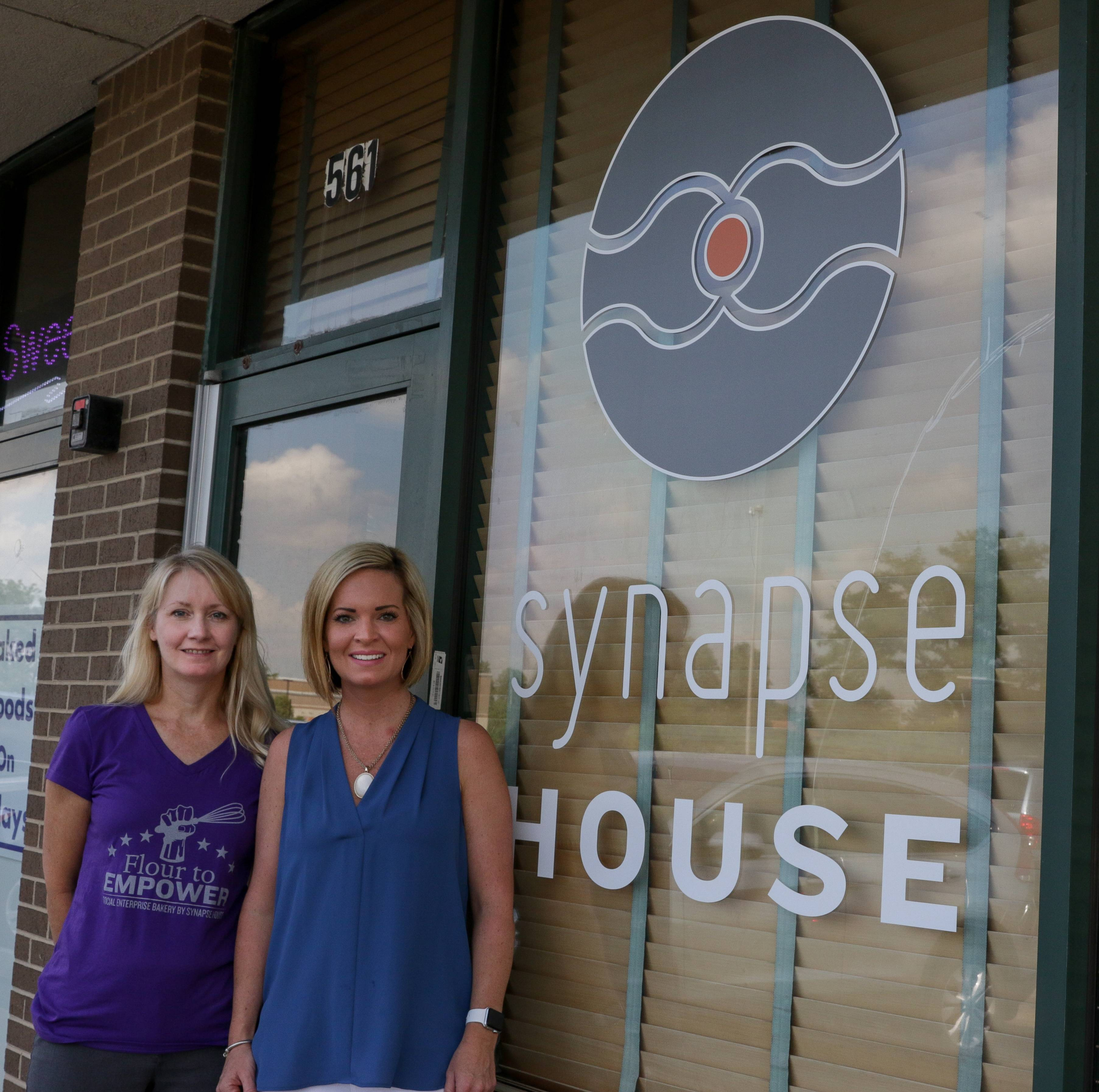 Deborah Giesler, director of Synapse House in Elmhurst, left, with Becky Kostelny of Elmhurst Junior Women's Club, right. The club raised $18,663 to buy a sign for Synapse House.