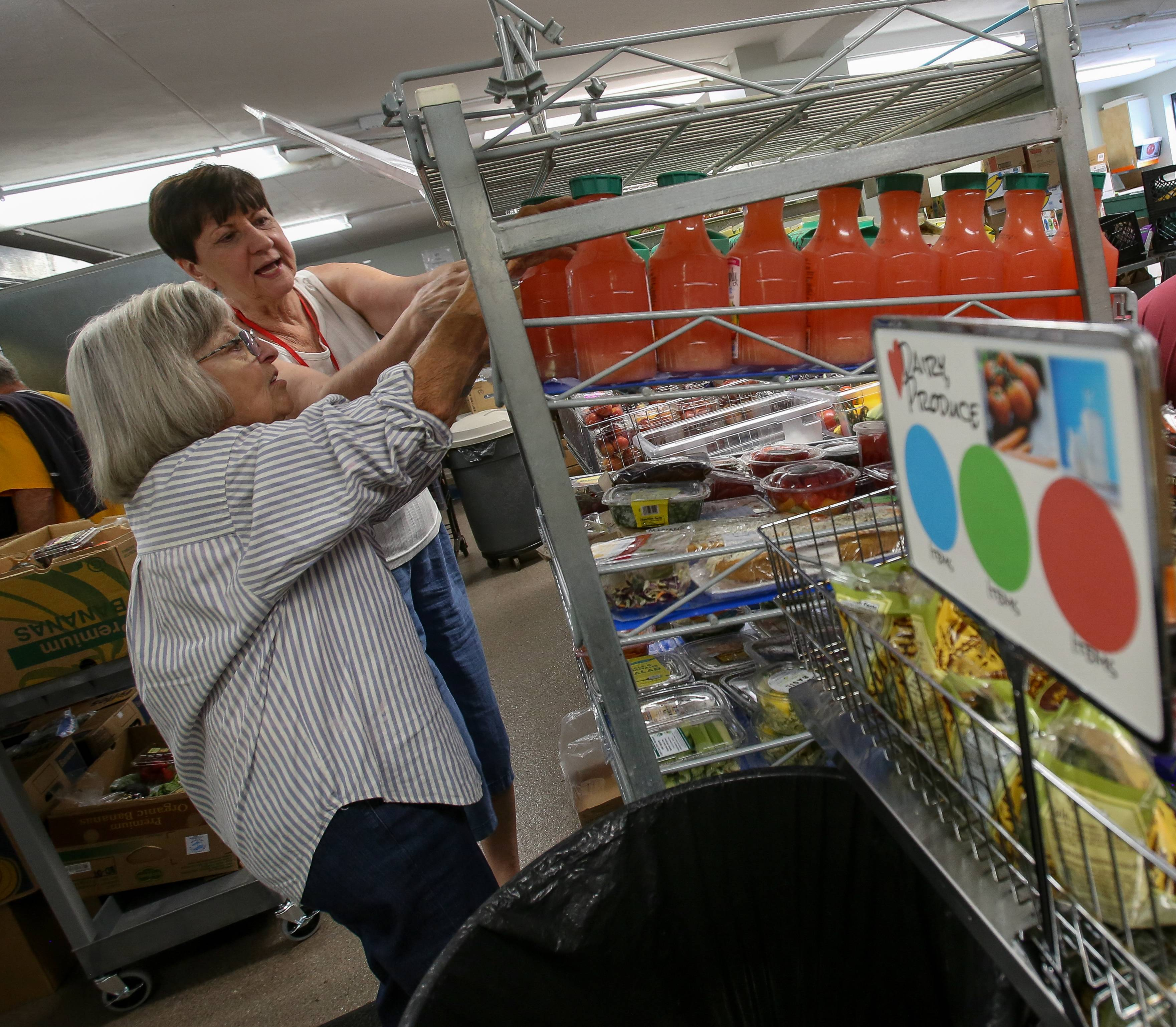 Volunteers Diane Lynch of Wheaton and Ruth Zumpano of Carol Stream, right, get groceries ready at the new-look food pantry in the People's Resource Center in Wheaton. The pantry had been closed since July 25.