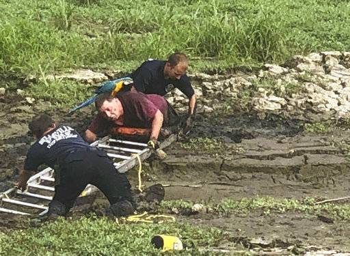 Man rescued from mud with parrot perched on his shoulders