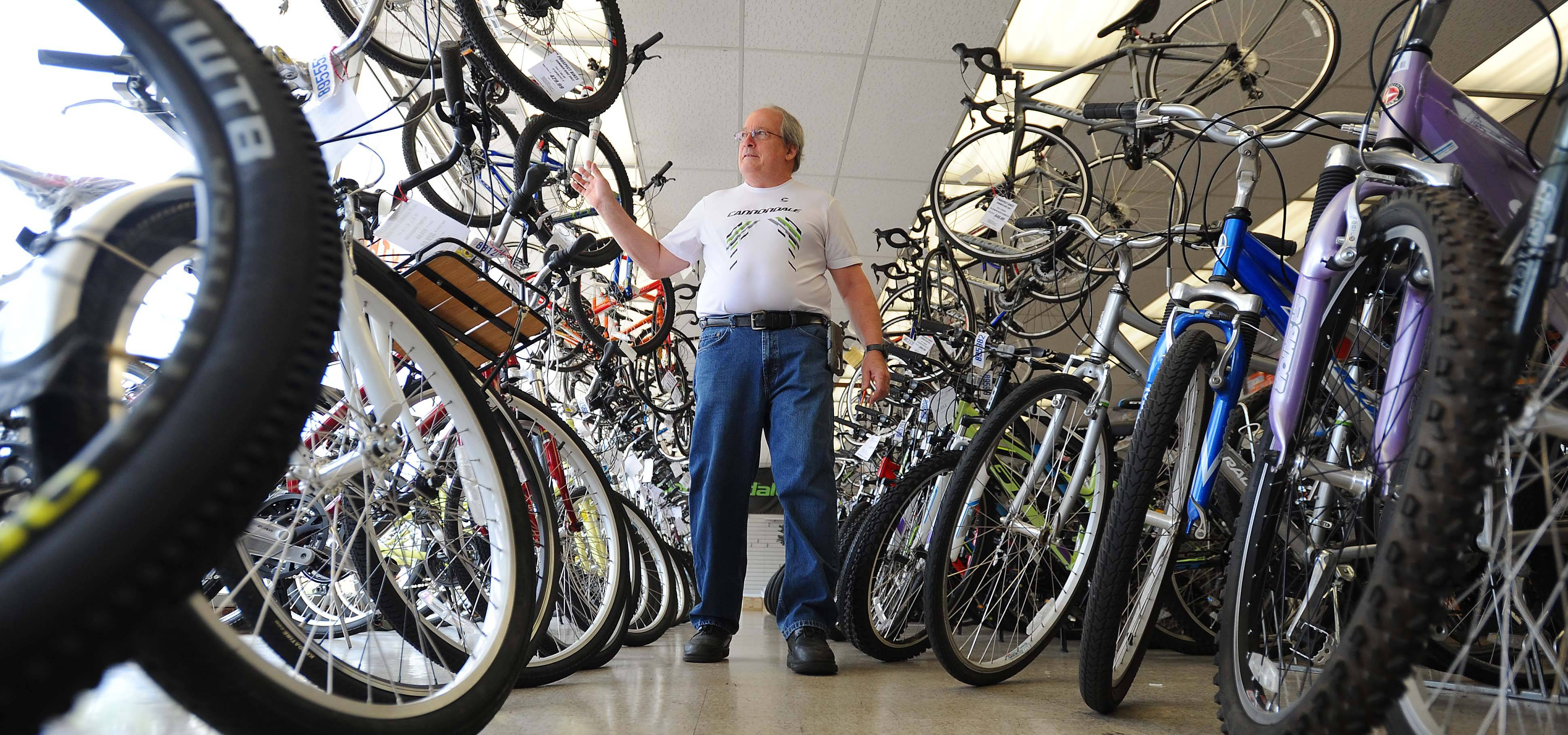 Bill Schmoldt, owner of Prospect Bikes in Mount Prospect waves to a fellow bike rider outside as he inspects his inventory of bikes he will be selling this month before closing the shop he has run since 1979.