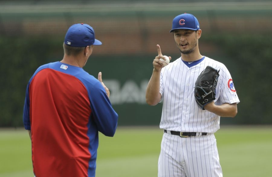 Cubs pitcher Yu Darvish, who threw a simulated game Tuesday, talks with pitching coach Jim Hickey during another simulated game in June.