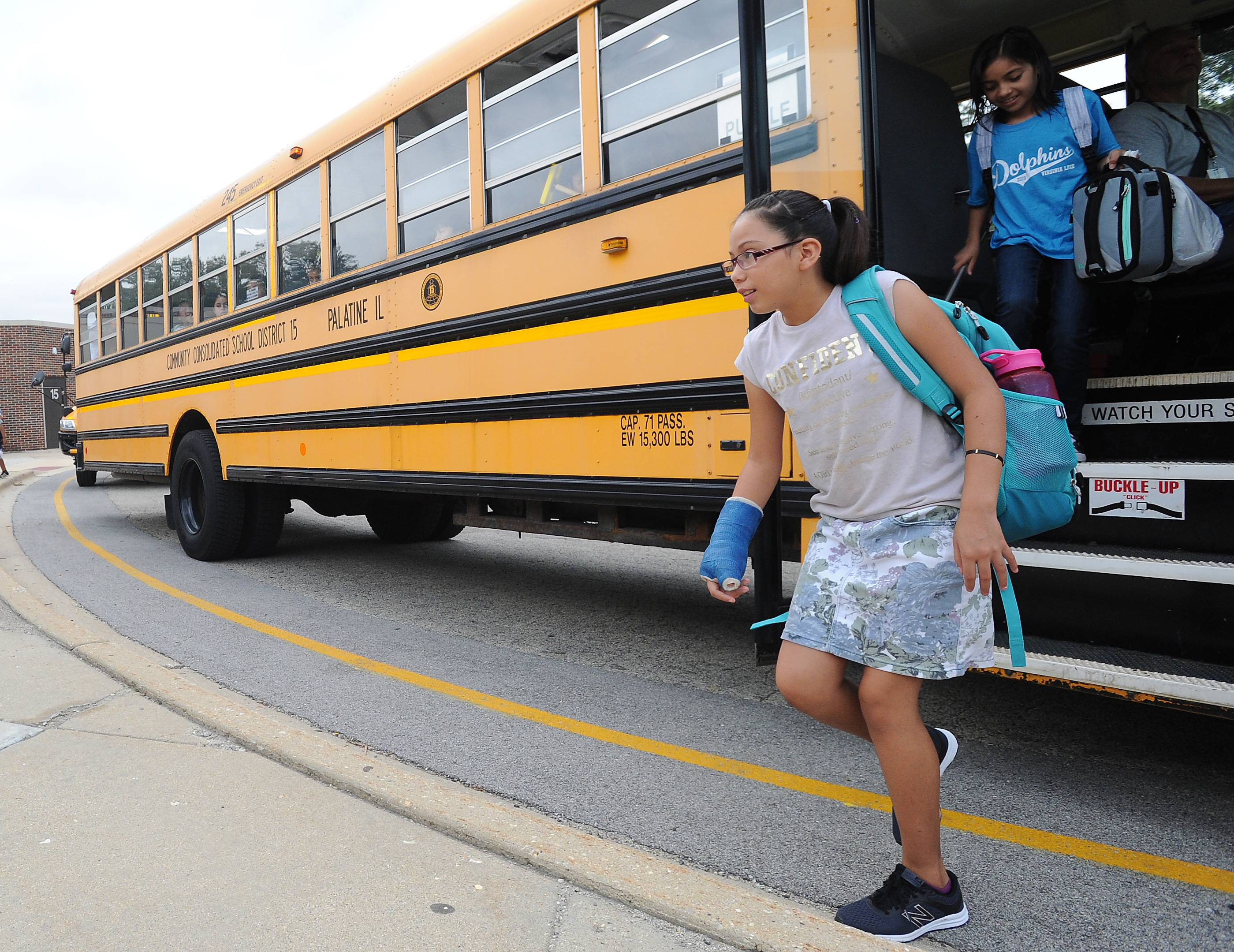 """It's cool"" is how Lailany Murillo, 10, of Palatine describes her first day of school at Virginia Lake Elementary School in Palatine as she gets off the bus before heading off to class Wednesday."