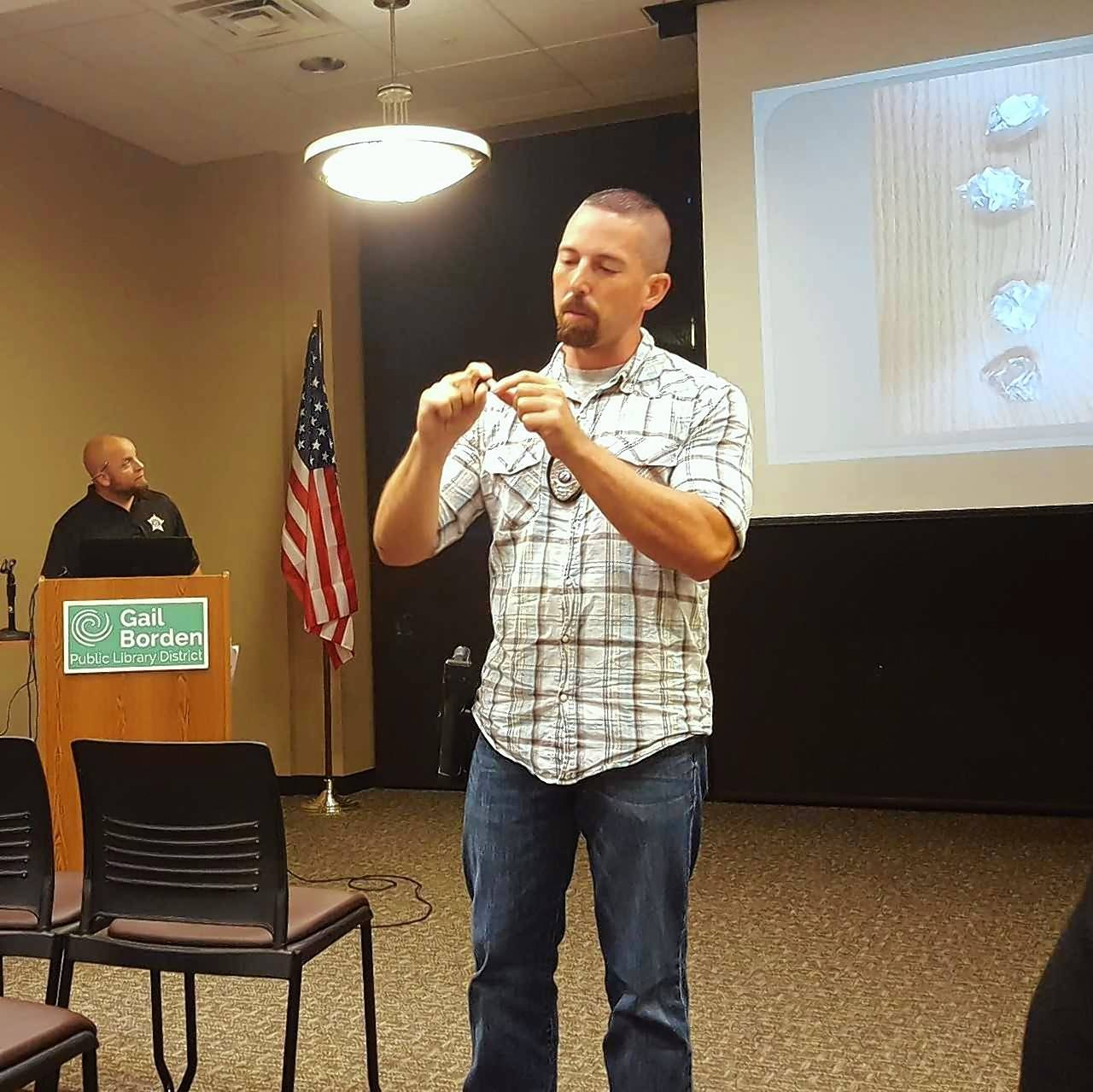 "Elgin Police Detective Anthony Rigano shows attendees at a ""Heroin Highway"" presentation Tuesday at the Gail Borden Public Library how a seemingly innocuous clear pill capsule can be used to hide and transport heroin."