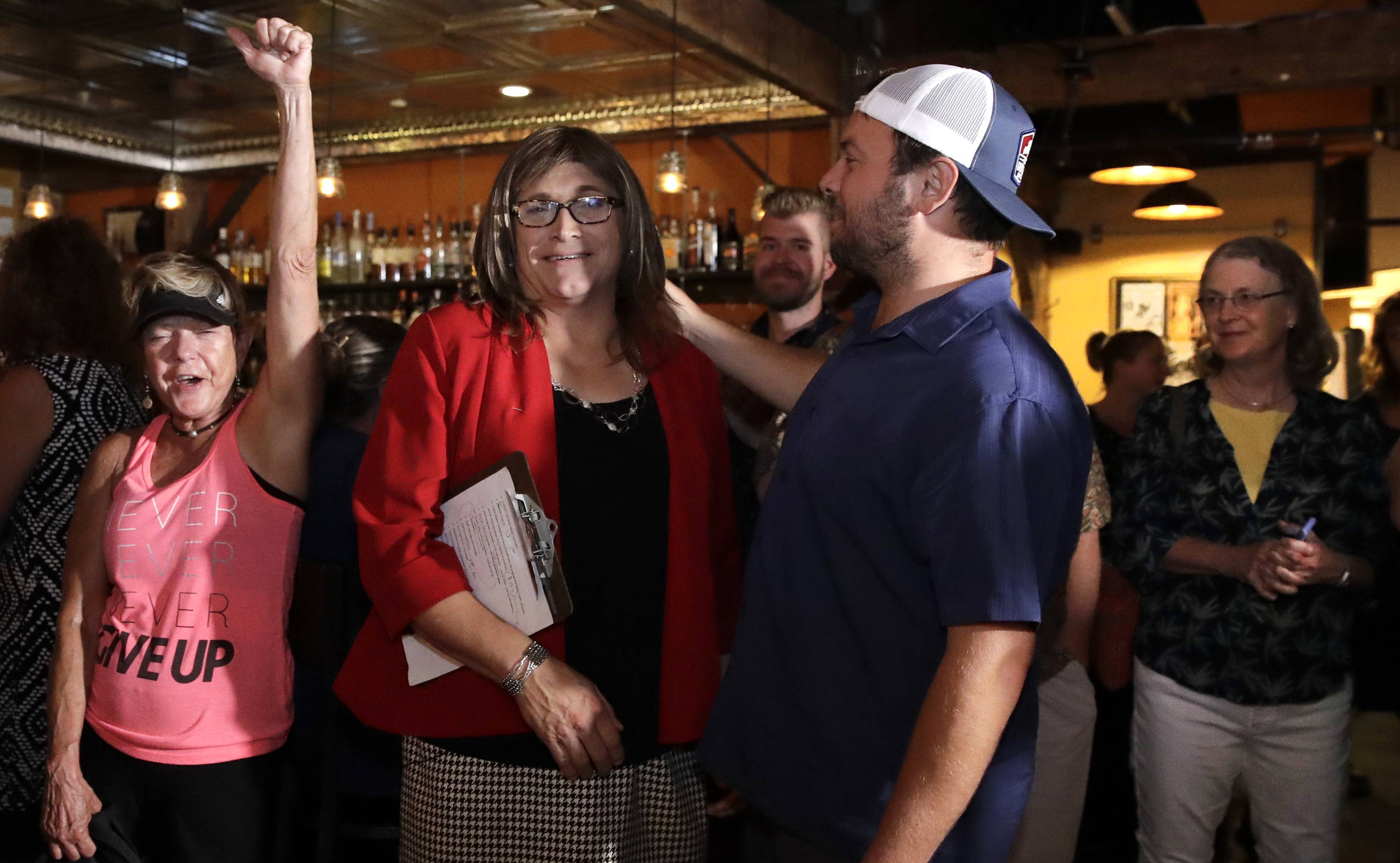 Vermont Democratic gubernatorial candidate Christine Hallquist, center, a transgender woman and former utility executive, is greeted by her supporters during her election night party in Burlington, Vt., Tuesday, Aug. 14, 2018. (AP Photo/Charles Krupa)