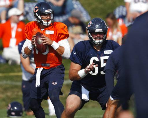 Chicago Bears quarterback Mitchell Trubisky, left, looks to pass the ball after taking a snap from center Cody Whitehair as they take part in drills during a joint NFL football training camp session with the Denver Broncos Thursday, Aug. 16, 2018, at Broncos' headquarters in Englewood, Colo. (AP Photo/David Zalubowski)