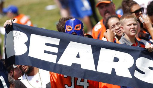 Jon Huvek, a Chicago native who now calls Fort Collins, Colo., home, calls to Chicago Bears players to sign autographs after drills during a joint NFL football training camp session with the Denver Broncos Wednesday, Aug. 15, 2018, at Broncos' headquarters in Englewood, Colo.