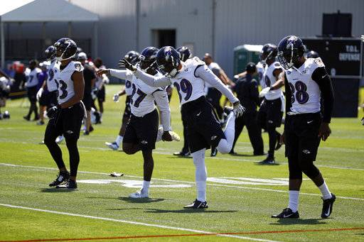 FILE - In this July 19, 2018, file photo, Baltimore Ravens cornerbacks Jackson Porter, from left, Darious Williams, Bennett Jackson and Stanley Jean-Baptiste stretch during an NFL football training camp practice at the team's headquarters in Owings Mills, Md. In recent years, the presence of yoga has grown in the NFL. The fast-paced, hard-hitting sport has accepted the more calming practice that emphasizes conscious breathing and body flow. Much like yin and yang, the two complement each other both mentally and physically. (AP Photo/Patrick Semansky, File)