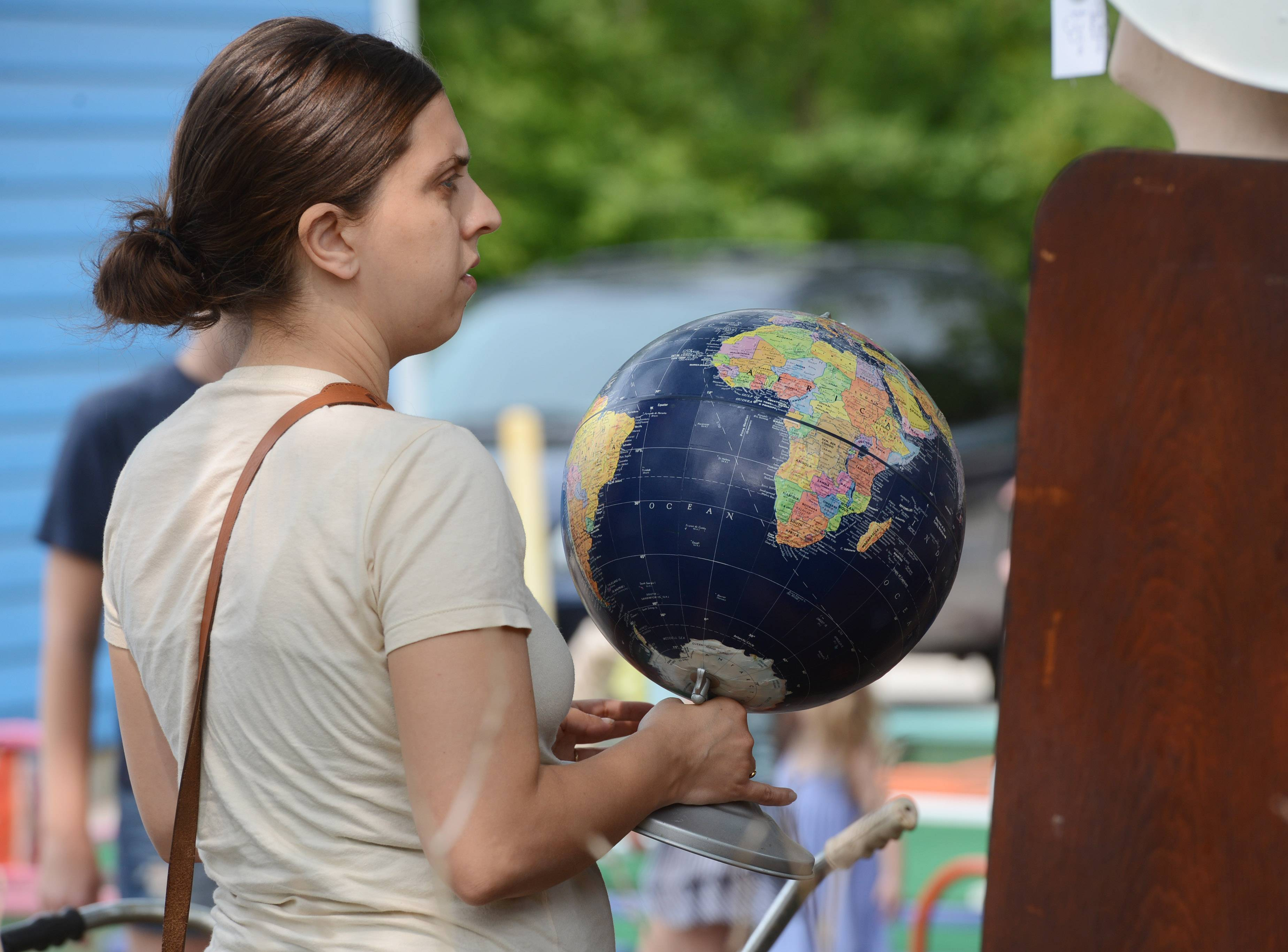 Alicia Abood of Libertyville holds a globe displayed for sale during Long Grove Vintage Days Saturday.