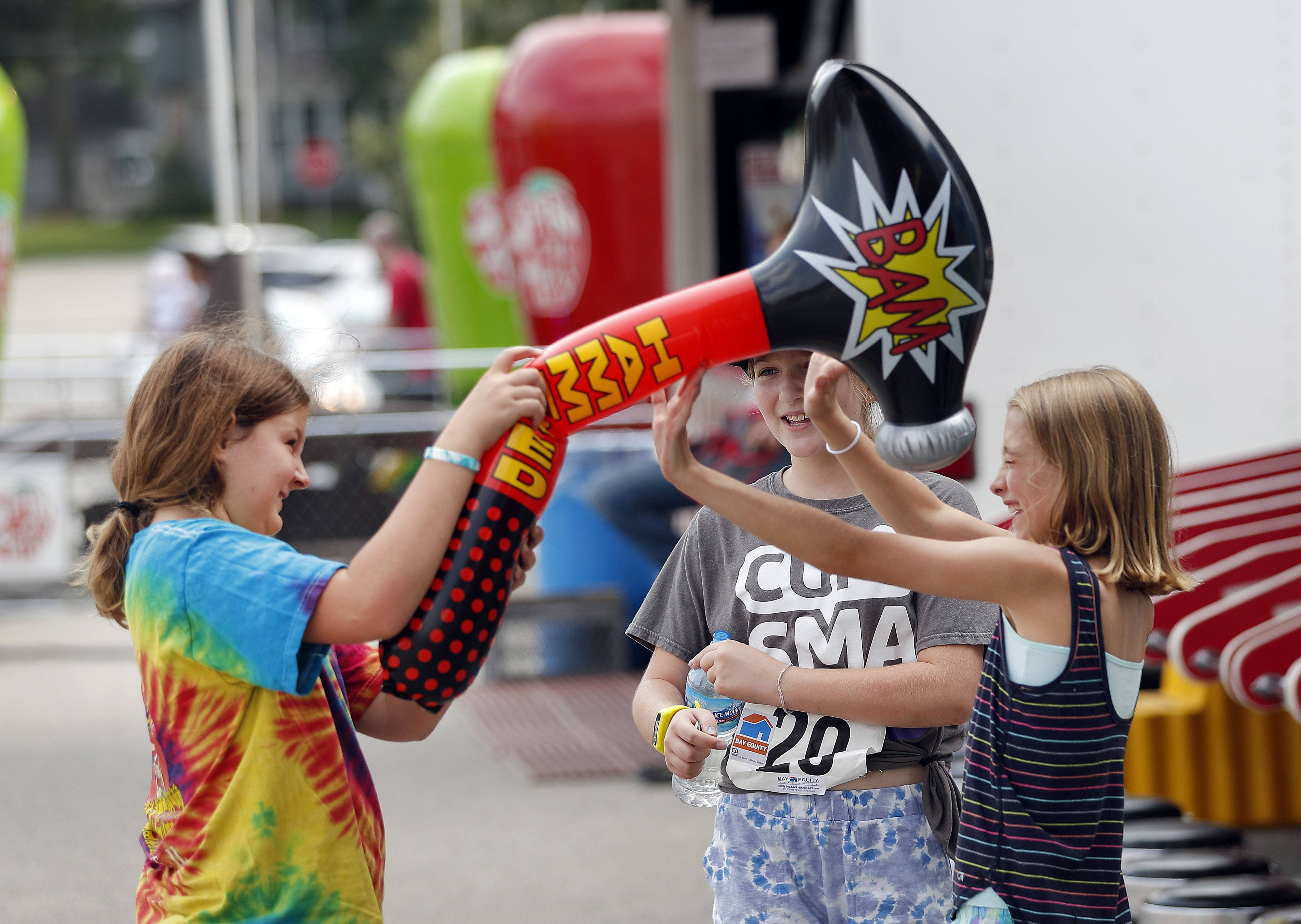 From left Taylor Schoenborn, Sofi Brown and Sydney Brown, all 10 and from Grayslake, play with a toy they won from a carnival game during the Grayslake Chamber of Commerce and Industry's Summer Days festival in downtown Grayslake Saturday.