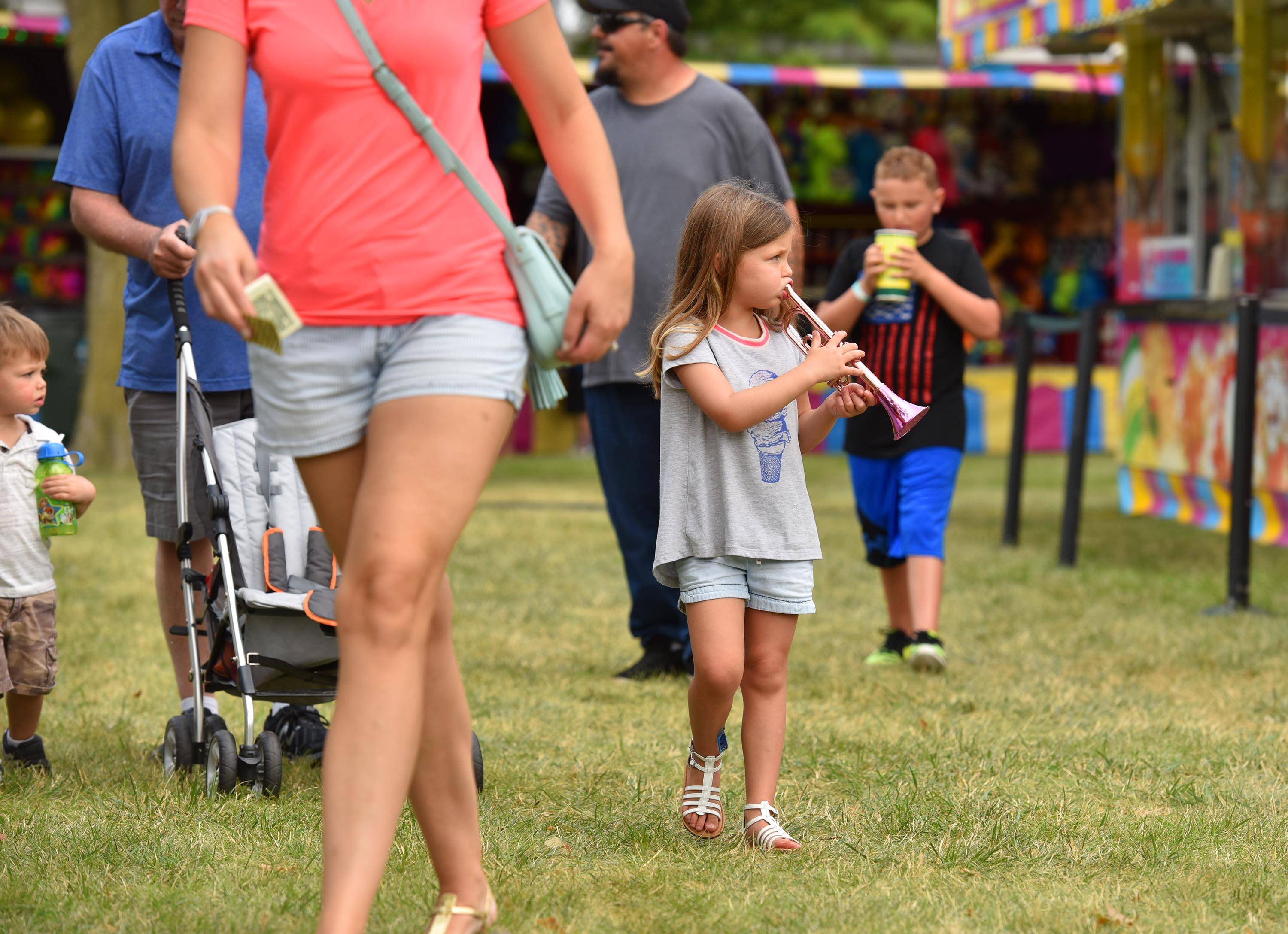 Violet Steinberg, 4, plays the plastic horn that she just won on the midway at the South Elgin Riverfest Express Saturday on the Fox River in South Elgin. She was with her family from St. Charles.