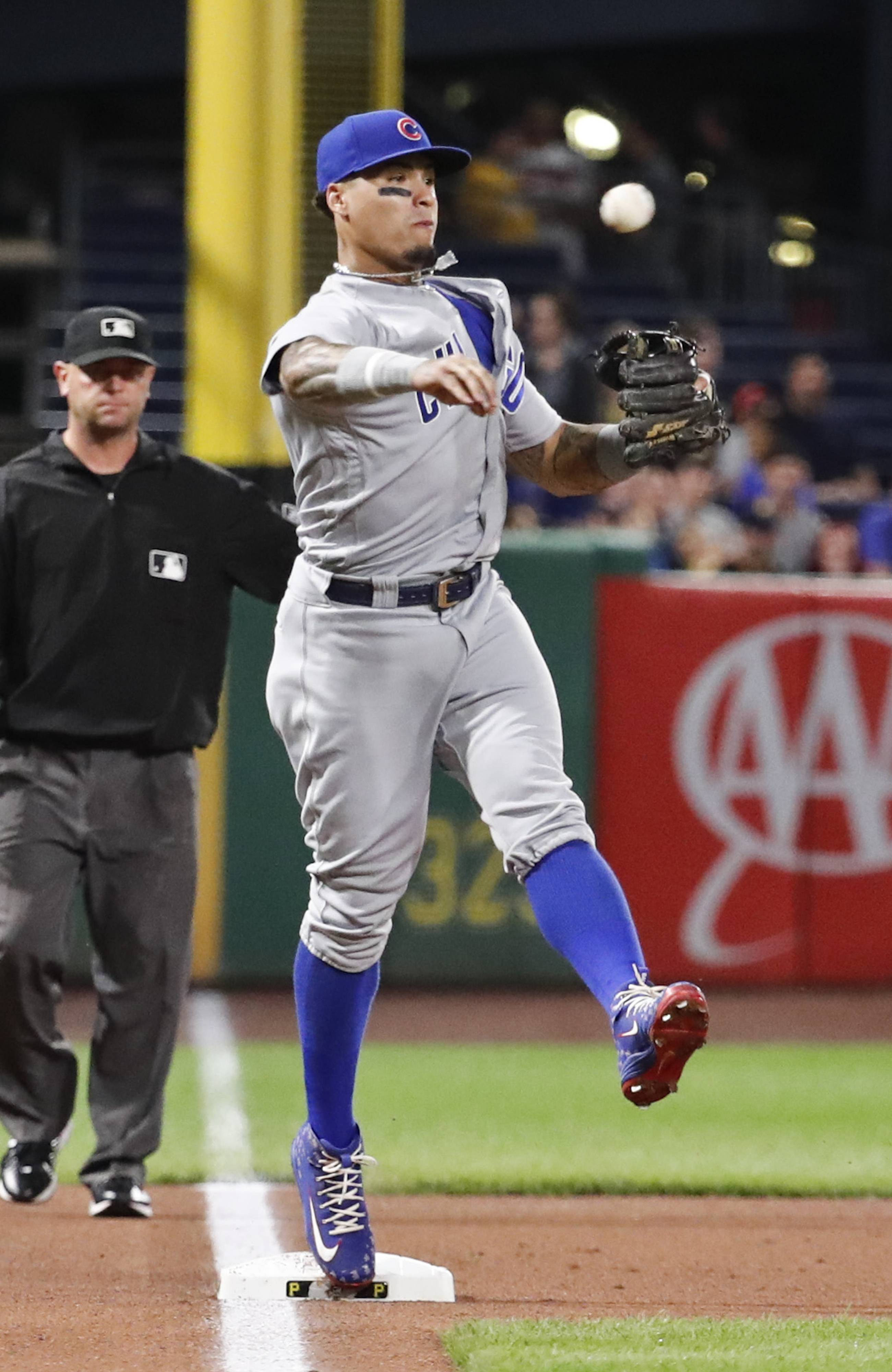 Chicago Cubs third baseman Javier Baez throws to first to complete a double play on Pittsburgh Pirates' David Freese after forcing out Starling Marte at third to end the first inning of a baseball game Friday, Aug. 17, 2018, in Pittsburgh.
