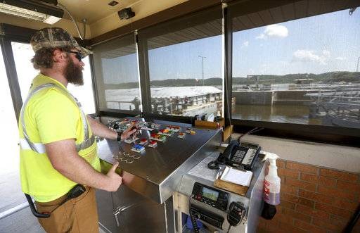 In this Wednesday, Aug. 1, 2018, photo, Steven Moellers controls gates at Lock and Dam No. 11 in Dubuque, Iowa. The lock-and-dam structures in Dubuque, Bellevue and Guttenberg, Iowa, were completed in the late 1930s. All three have stood for 80 years, despite being designed with only a 50-year life expectancy. The U.S. Army Corps of Engineers has kept the system humming along through rigorous maintenance. However, there is no plan in place for the replacement of the structures - which increasingly is raising concerns. (Jessica Reilly/Telegraph Herald via AP)