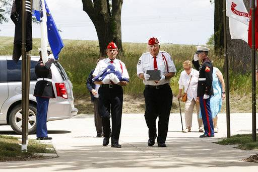 "In this July 19, 2018 phot, Abraham Lincoln National Cemetery Memorial Squad members  George Anthos, left, carries the American flag while Lou Bush, right, carries the remains of a deceased Marine during a service ""Honoring Those Who Served,"" at the cemetery in Elwood, Ill. About three dozen of the group's volunteers accompany veterans on their last journey. They present the colors, play taps, fire 21-shot salutes and present U.S. flags to survivors. (Daniel White/Daily Herald, via AP)"