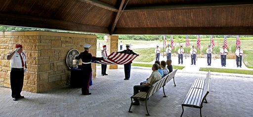 "In this July 19, 2018 photo, Abraham Lincoln National Cemetery Memorial Squad members  Lou Bush and George Anthos salute while the American flag is folded and family members observe during a service ""Honoring Those Who Served,"" at the cemetery in Elwood, Ill. About three dozen of the group's volunteers accompany veterans on their last journey. They present the colors, play taps, fire 21-shot salutes and present U.S. flags to survivors. (Daniel White/Daily Herald, via AP)"