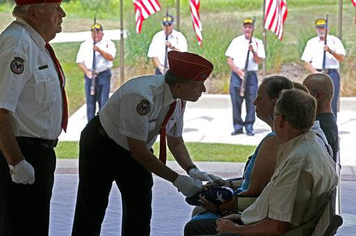 "In this July 19, 2018 phot, Abraham Lincoln National Cemetery Memorial Squad member  George Anthos, Navy veteran, presents the American flag along with a pack of three spent shells that represent the volley of the 21 gun salute to a family during a service ""Honoring Those Who Served,"" at the cemetery in Elwood, Ill. About three dozen of the group's volunteers accompany veterans on their last journey. They present the colors, play taps, fire 21-shot salutes and present U.S. flags to survivors. (Daniel White/Daily Herald, via AP)/"