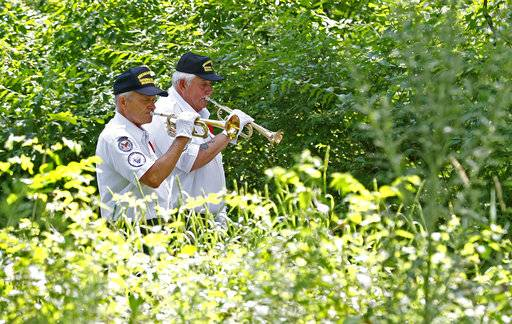 "In this July 19, 2018 photo, Abraham Lincoln National Cemetery Memorial Squad members  Buglars Ed Crobie and Joe Gremal sound taps following a 21 gun salute during a service ""Honoring Those Who Served,"" at the cemetery in Elwood, Ill. About three dozen of the group's volunteers accompany veterans on their last journey. They present the colors, play taps, fire 21-shot salutes and present U.S. flags to survivors. (Daniel White/Daily Herald, via AP)"