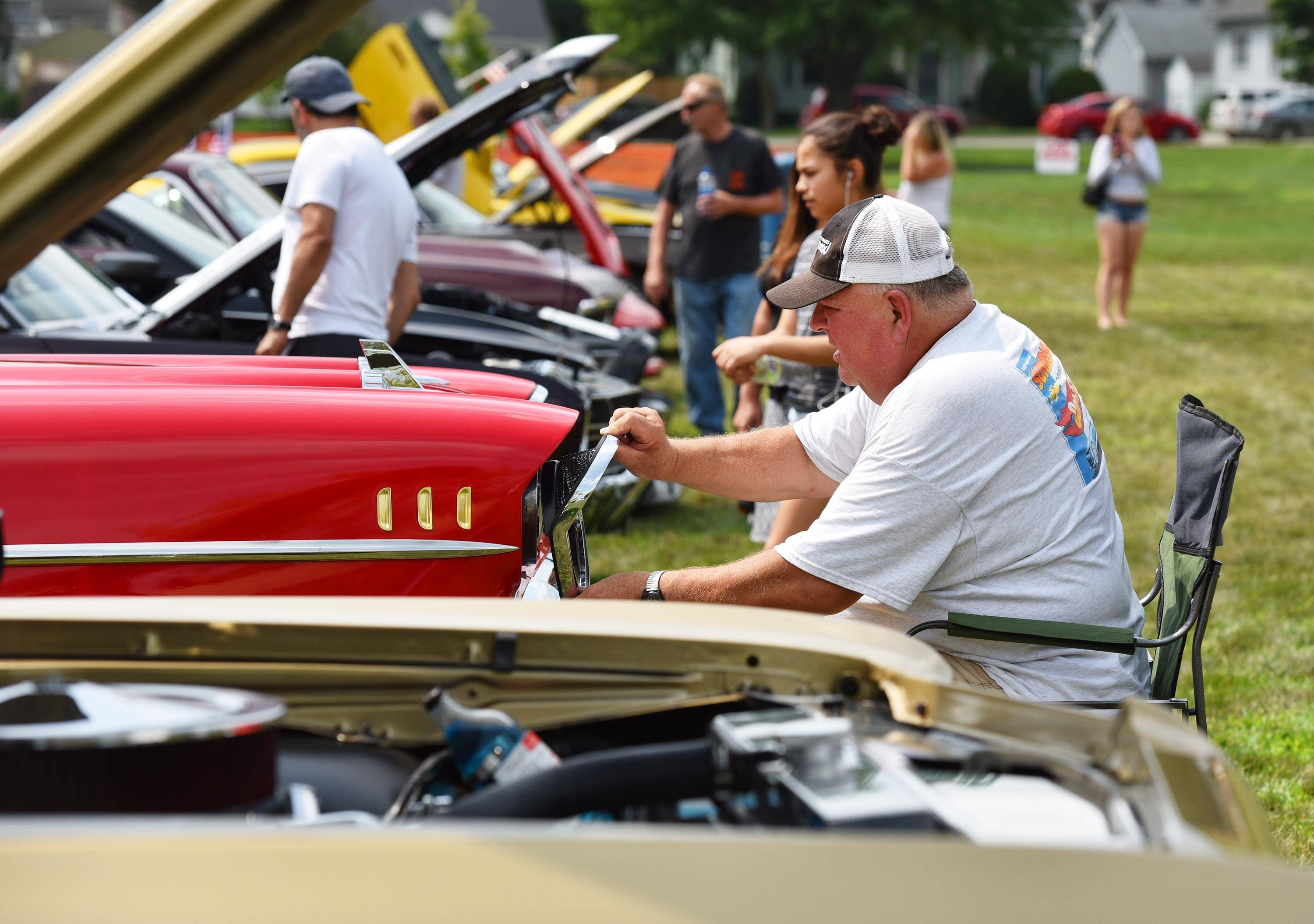 Wayne Bastiaans replaces the headlight frame after adjusting the angle of the beam on his 1957 Chevy Bel Air at a car show at the Rock the Fox festival, sponsored by Oddfellows Century Lodge 492, in Carpenter Park in Carpentersville Saturday. Bastiaans is from Carpentersville and has owned the car for 18 years.