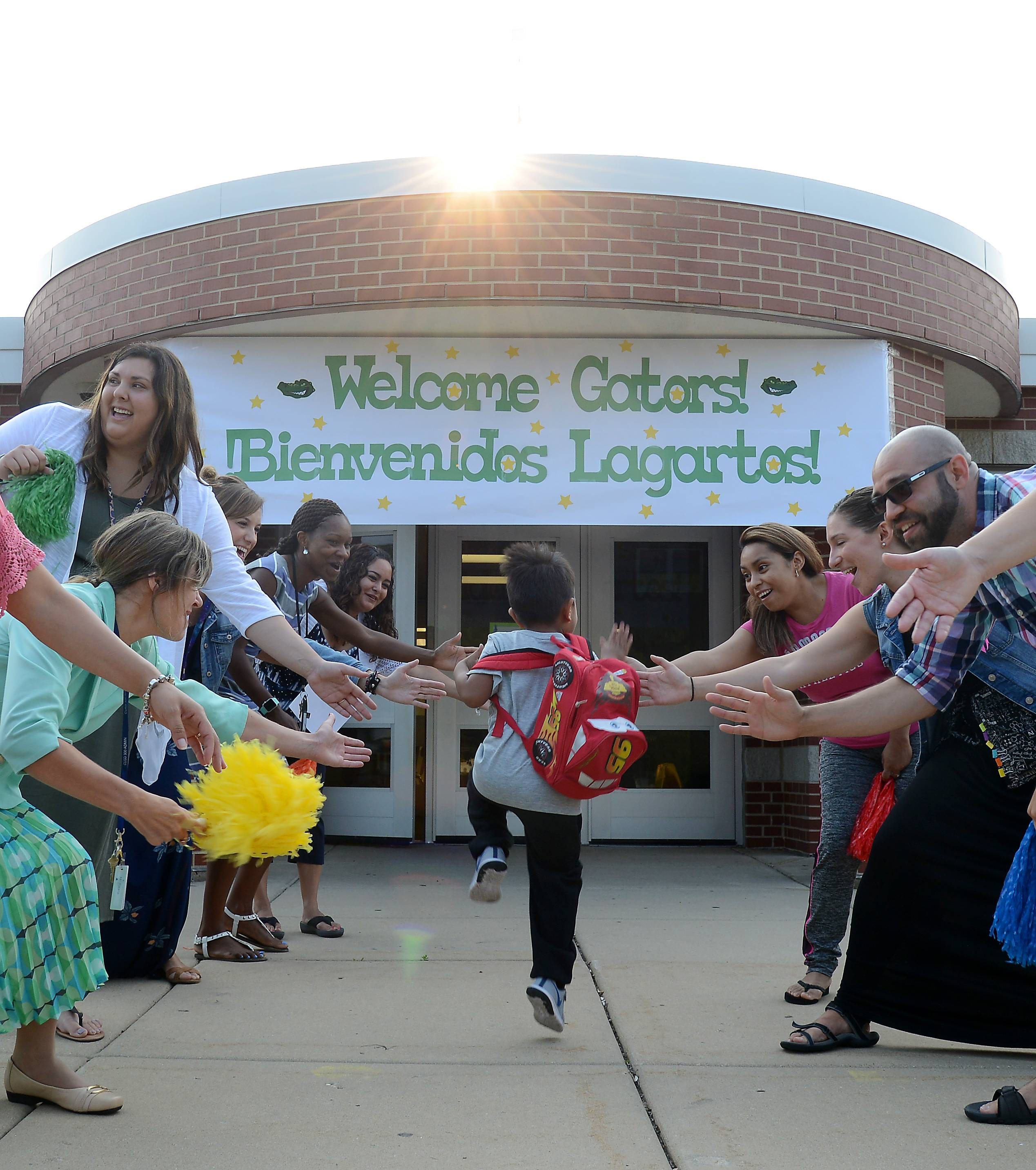 Teachers and faculty give high-fives and greet kids as they arrive for the first day of classes at Golfview Elementary School in Carpentersville. It was the first day for students throughout Community Unit District 300.