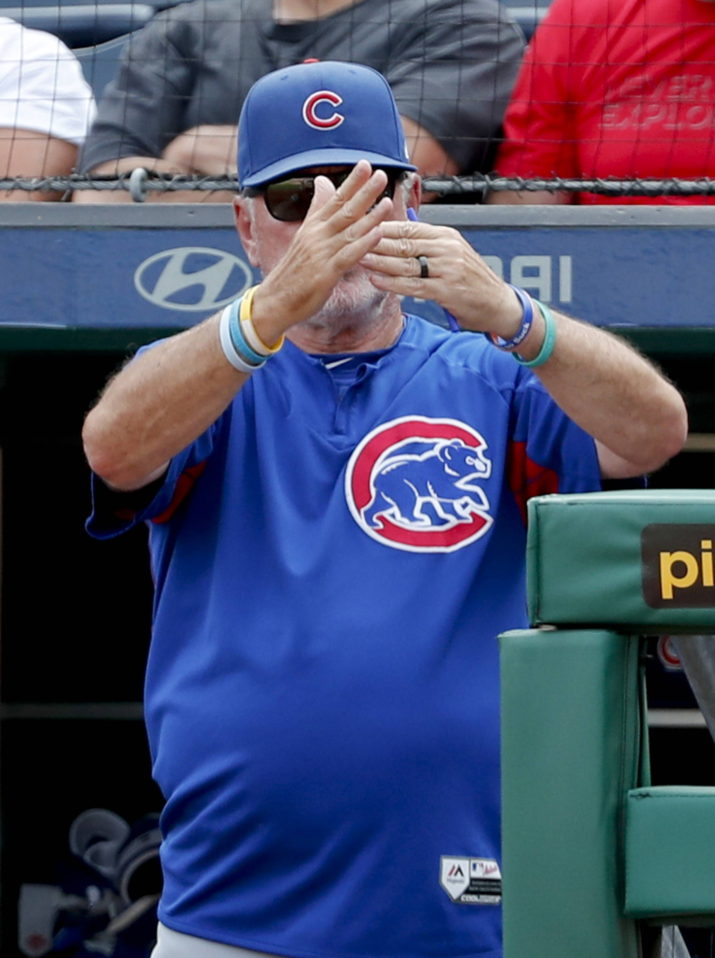 Chicago Cubs manager Joe Maddon call for a timeout with the bases loaded to pull the outfield in and have an outfielder change gloves as the Pittsburgh Pirates bat in the ninth inning of a baseball game Sunday, Aug. 19, 2018, in Pittsburgh. (AP Photo/Keith Srakocic)