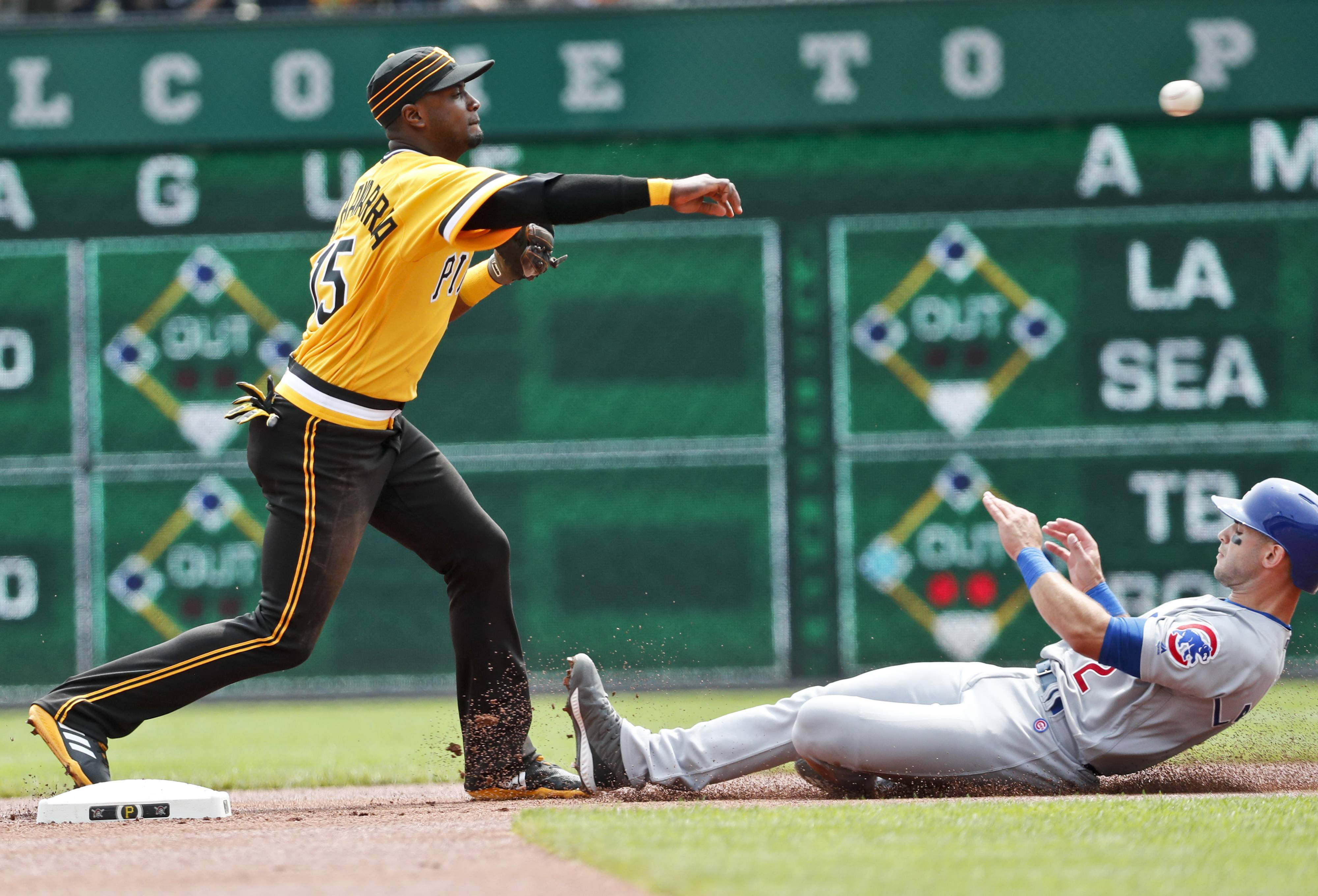 Pittsburgh Pirates shortstop Adeiny Hechavarria, left, relays on to to first after forcing Chicago Cubs' Tommy La Stella out at second to complete the double play on Ben Zobrist in the first inning of a baseball game, Sunday, Aug. 19, 2018, in Pittsburgh.