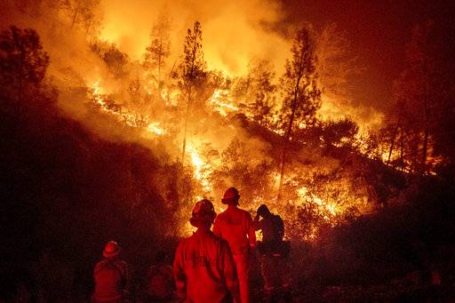 FILE - In this Aug. 7, 2018 file photo, firefighters monitor a backfire while battling the Ranch Fire, part of the Mendocino Complex Fire near Ladoga, Calif. The years with the most acres burned by wildfires have some of the hottest temperatures, an Associated Press analysis of fire and weather data found. As human-caused climate change has warmed the world over the past 35 years, the land consumed in flames has more than doubled. (AP Photo/Noah Berger)