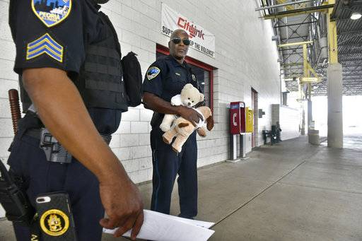 In this Aug. 2, 2018 photo, Peoria police officer Curtis Lindsay talks with another officer as he waits for buses to arrive at the CityLink Mass Transit Center to hand out stuffed animals to children in Peoria, Ill. Lindsay has been passing to stuffed animals to children he encounters for the past year while on his rounds. (David Zalaznik/Journal Star via AP)