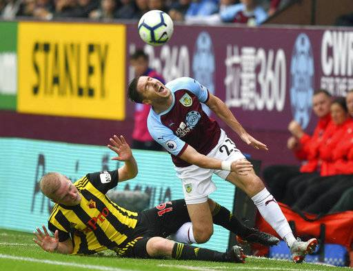 Watford's Will Hughes, left, tackles Burnley's Stephen Ward, during their English Premier League soccer match at Turf Moor in Burnley, England, Sunday Aug. 19, 2018. (Dave Howarth/PA via AP)