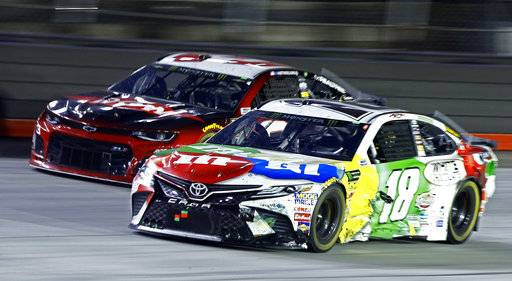 Kyle Busch (18) gets past Austin Dillon during the NASCAR Cup Series auto race, Saturday, Aug. 18, 2018, in Bristol, Tenn. (AP Photo/Wade Payne)