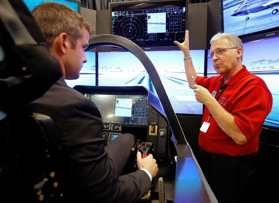 Lockheed Martin systems engineer Dennis Littrell, right, explains the instrumentation of the F-35 fighter jet simulator to U.S. Rep. Adam Kinzinger at UTC Aerospace Systems in Rockford.