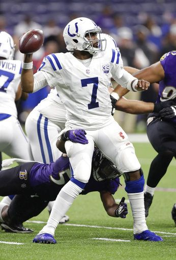 Indianapolis Colts quarterback Jacoby Brissett (7) throws a completion as he is hit by Baltimore Ravens linebacker Tim Williams (56) during the second half of an NFL preseason football game in Indianapolis, Monday, Aug. 20, 2018.