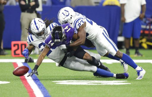 Baltimore Ravens wide receiver Tim White (14) fumbles on a punt return as he is hit by Indianapolis Colts defensive back Clayton Geathers (26) and cornerback Kenny Moore (23) in the first half of an NFL preseason football game in Indianapolis, Monday, Aug. 20, 2018.
