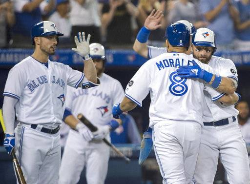 Toronto Blue Jays designated hitter Kendrys Morales (8) celebrates with centre fielder Kevin Pillar, right, and teammates after hitting a three run home run against the Baltimore Orioles during fifth inning baseball action in Toronto on Monday, Aug. 20, 2018. (Nathan Denette/The Canadian Press via AP)