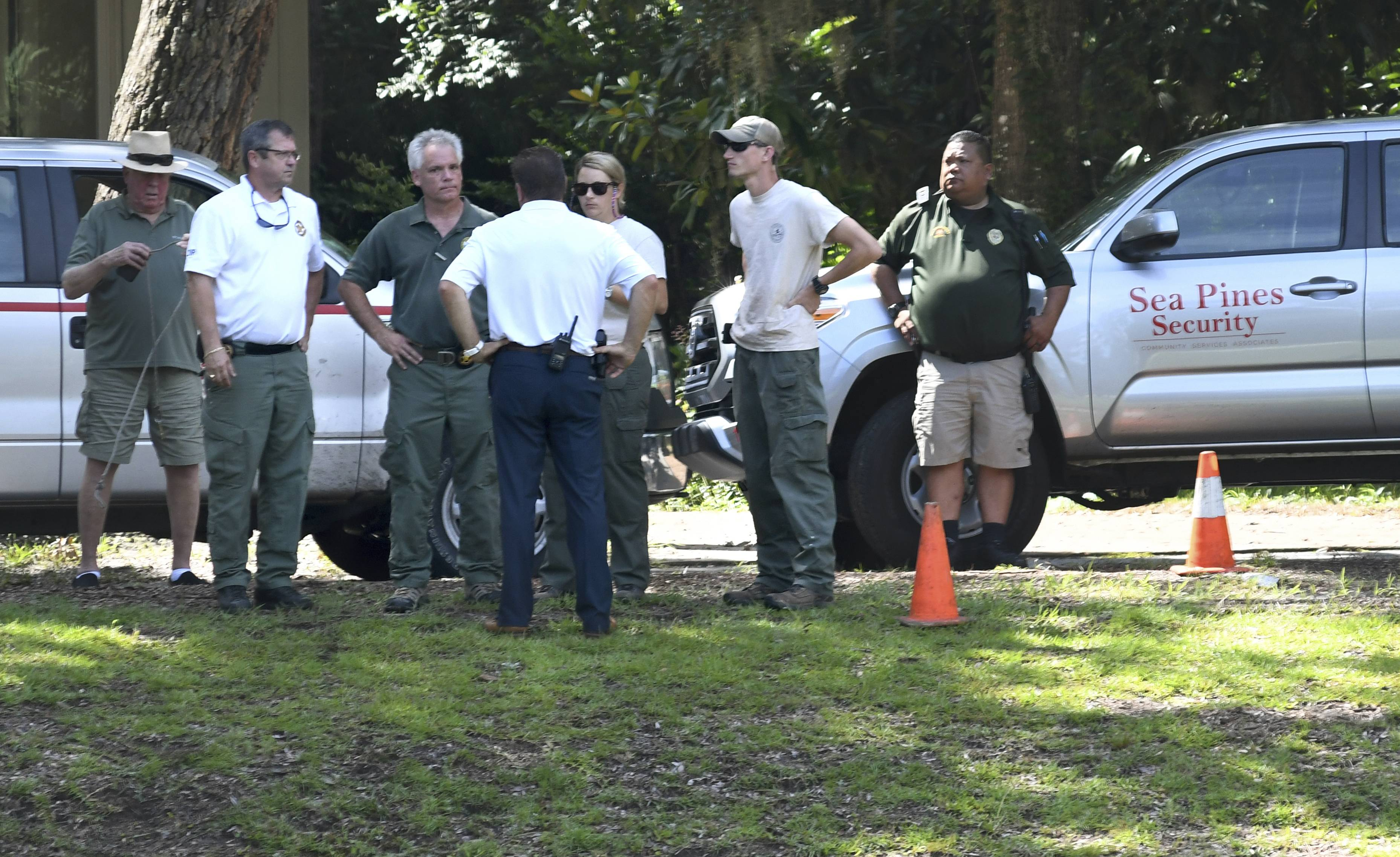 Law enforcement with Sea Pines Security, S.C. Department of Natural Resources and the Beaufort County Sheriff's Office stand near where authorities say Cassandra Cline was dragged into a lagoon by an alligator and killed while trying to save her dog on Monday, Aug. 20, 2018, on Hilton Head Island, S.C. Cline was walking the dog along a residential area of Sea Pines Resort when she was attacked, state and local officials said.