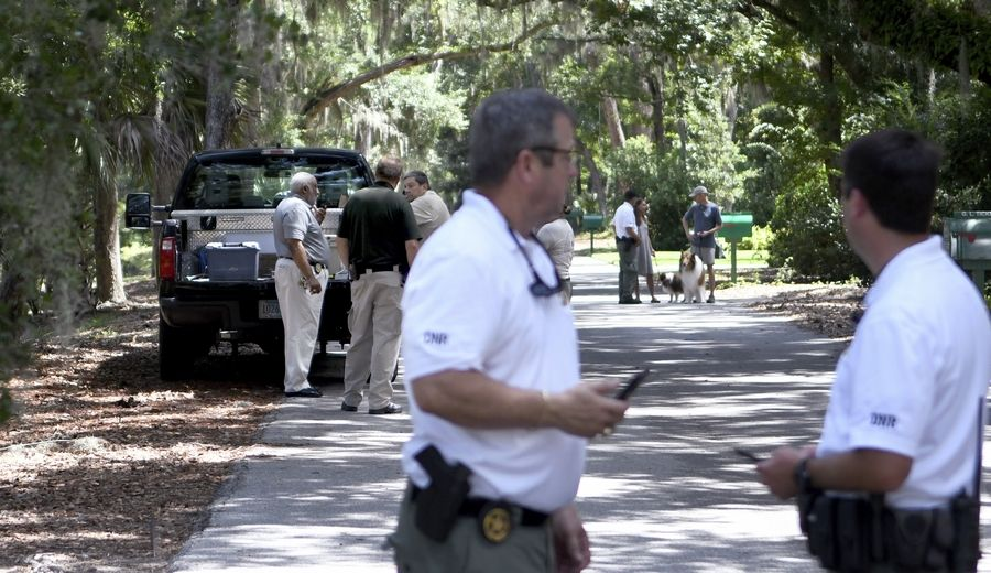 Beaufort County coroner Ed Allen, back left, talks with law enforcement with S.C. Department of Natural Resources as other officers stand near where authorities say Cassandra Cline was dragged into a lagoon by an alligator and killed while trying to save her dog Monday, Aug. 20, 2018, on Hilton Head Island, S.C. Cline was walking the dog along a residential area of Sea Pines Resort when she was attacked, state and local officials said.