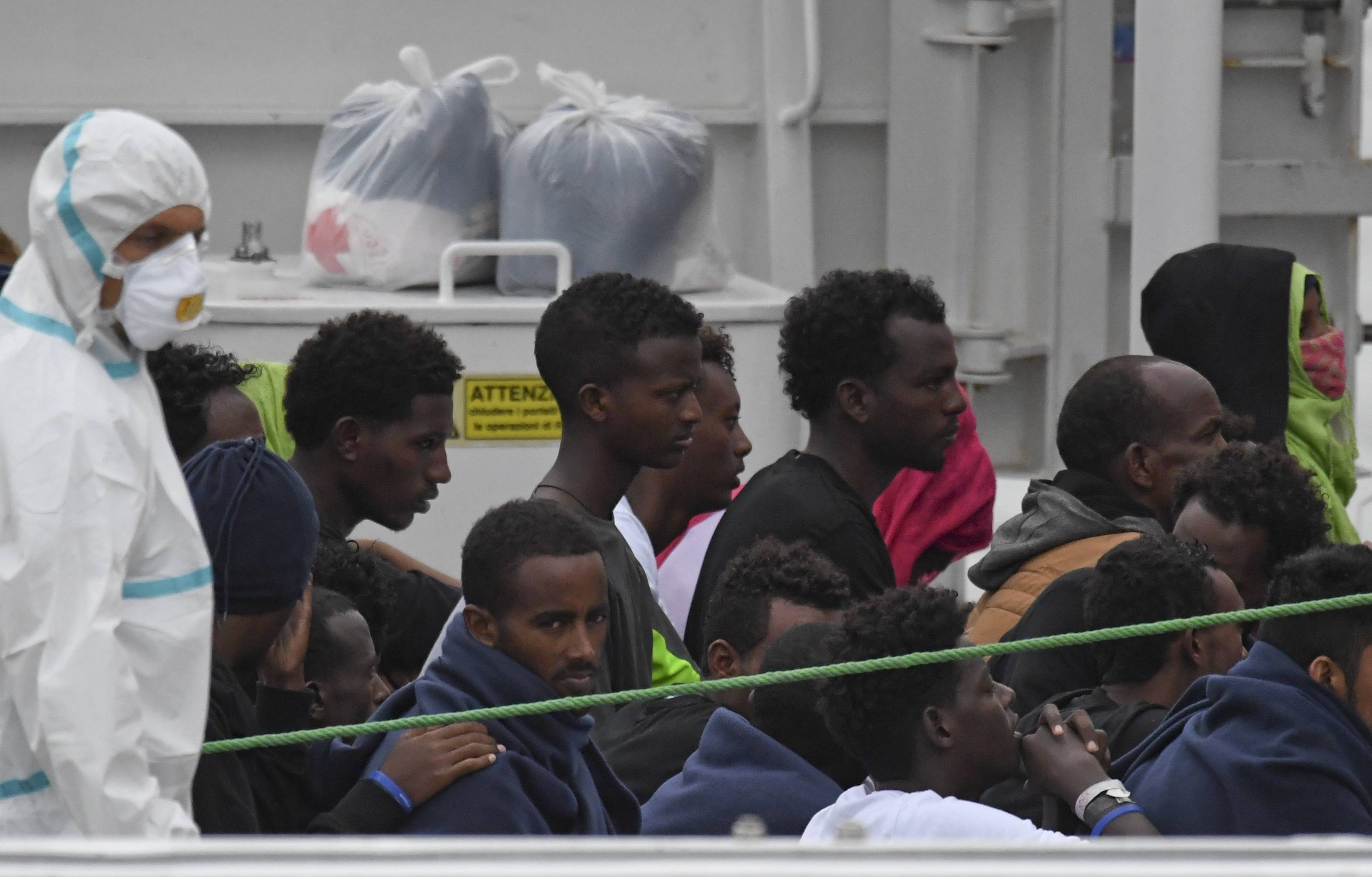 Migrants stand aboard the Italian Coast Guard ship Diciotti, moored at the Catania harbor, Tuesday, Aug. 21, 2018. One and seventy-seven migrants rescued at sea remained aboard the Italian Coast Guard ship Diciotti Tuesday morning as the Italian government refused to let them disembark in the port of Catania until other European countries agree to take them.The Diciotti arrived in the port of Catania late Monday night after spending days off the Italian coast as the Italian and Maltese government bickered over where they will be taken. (AP Photo/Salvatore Cavalli)