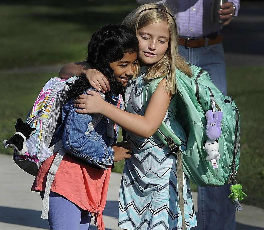 Violet Senne and Eden Mathai, both of Arlington Heights, greet one another with a hug Wednesday before beginning their first day of school at Longfellow Elementary School in Buffalo Grove.