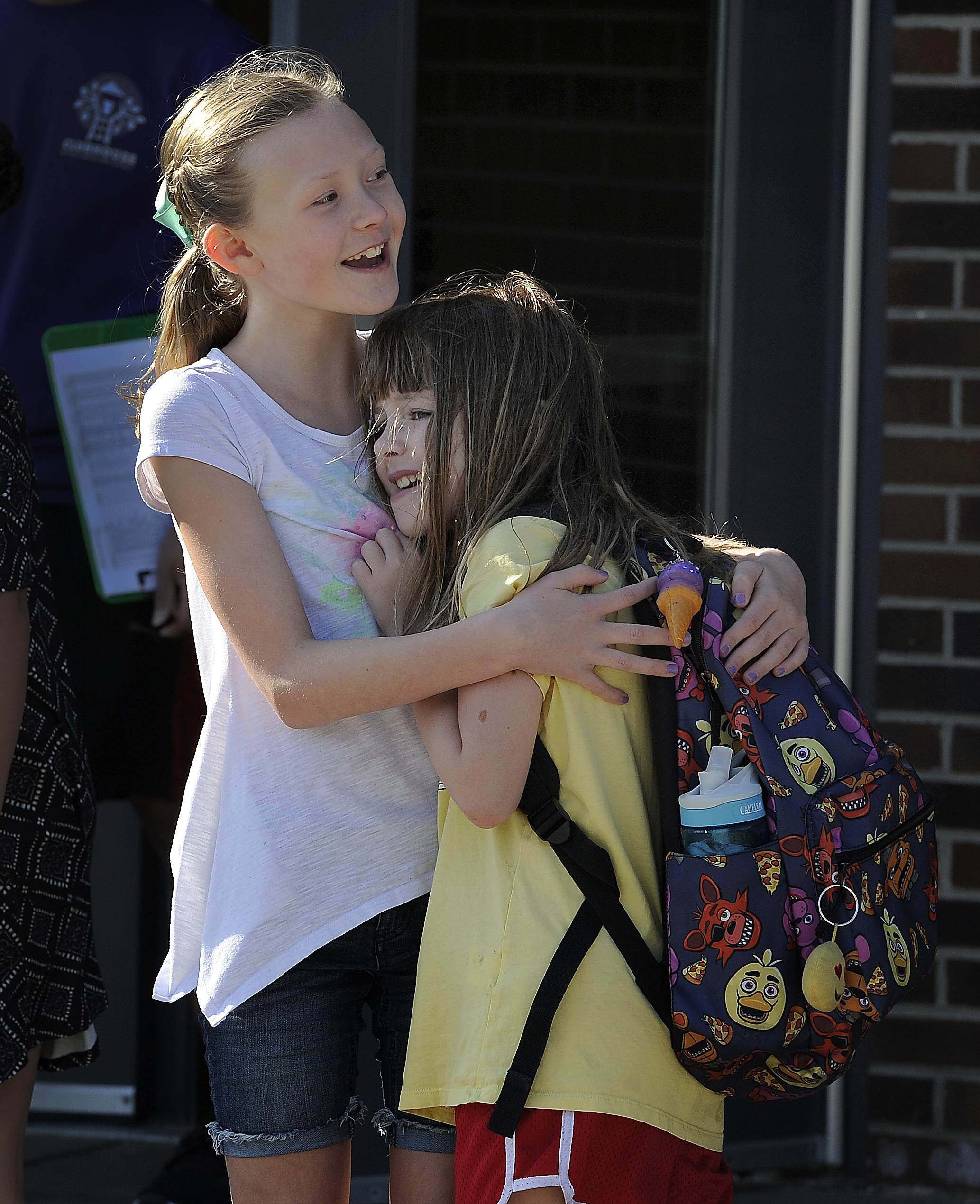 Kaden Monsen, 9, hugs Sari Baer, 11, as they head off to the fifth grade Wednesday at Longfellow Elementary School in Buffalo Grove.