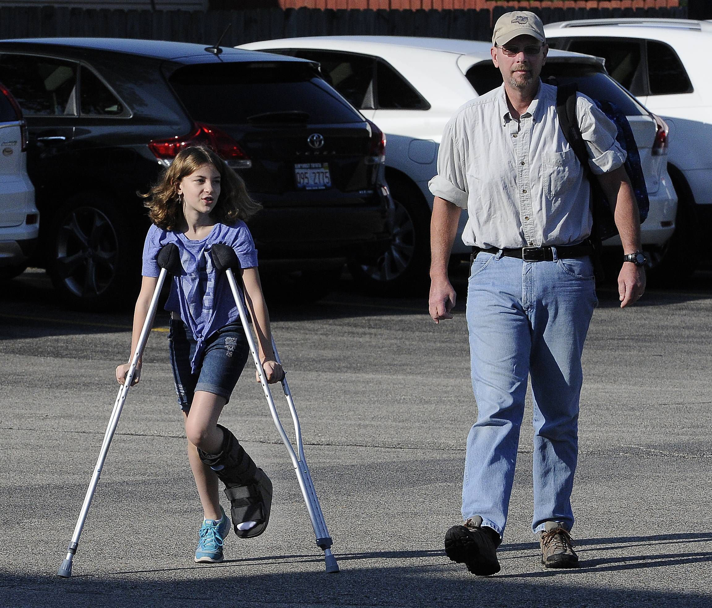 It was a tough way to greet the first day of school for Gwenyth Logan, 10, of Buffalo Grove as she has to deal with a stress fracture, but with the help of her dad, George, she makes it to her first day at Longfellow Elementary School in Buffalo Grove.