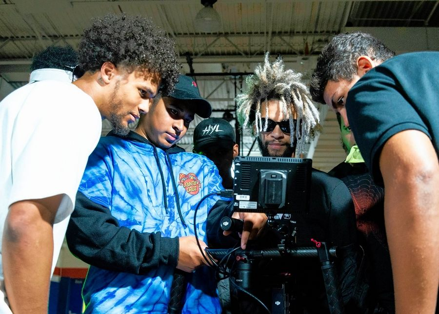 Members of The Future Kingz review footage of a video shot in the gym of Hoffman Estates High School.