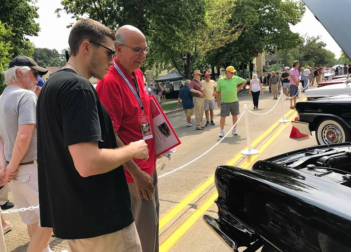 Noel Hastalis, one of the judges at the Geneva Concours d'Elegance, talks with Jack Maley of Geneva on Sunday about the Chrysler 300 series cars.