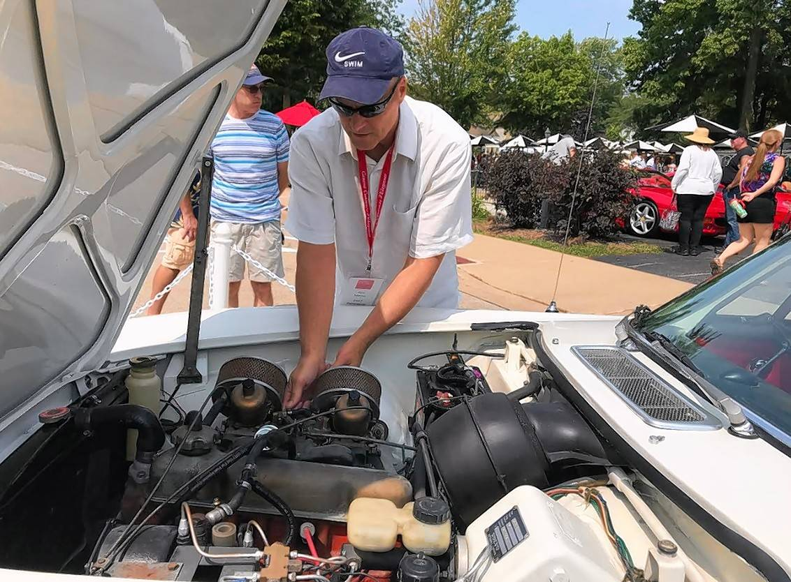 Ken Meyer of Woodstock reaches into the guts of his 1968 Volvo on Sunday during the Geneva Concours d'Elegance car show in the city's downtown.