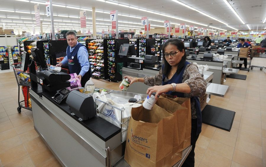 Rungrueang Nonthapha and Patrick Delaney practice bagging groceries Tuesday as they prepare for this week's opening of the new Woodman's Food Market in Buffalo Grove.