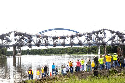 The old bridge carrying Illinois 104 over the Illinois River at Meredosia,Ill. falls into the river after being imploded Wednesday, Aug. 29, 2018 in Meredosia, Ill. The bridge, which opened in 1936, was replaced by new span this summer. (Rich Saal/The State Journal-Register via AP)