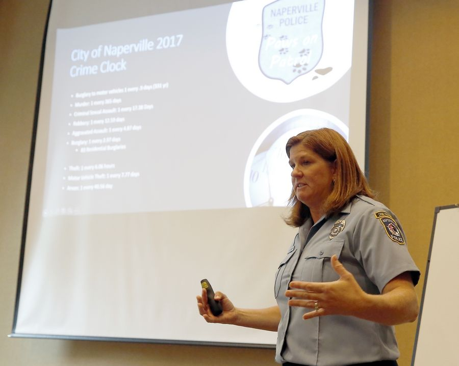 "Naperville Crime Prevention Officer Julie Smith talks about the department's new ""Paws on Patrol"" program with a couple dozen interested dog owners Wednesday. The program encourages people who are out walking their dogs to report suspicious activity."