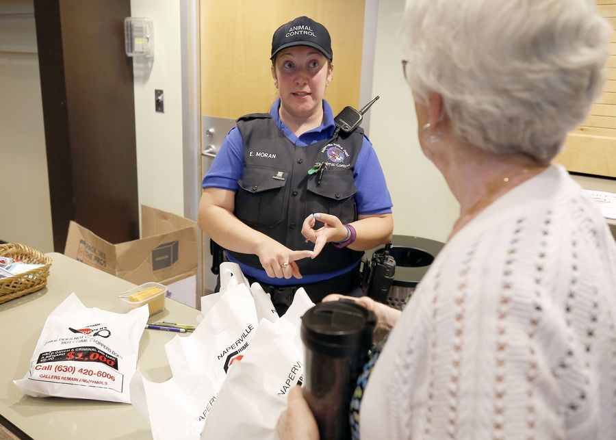 "Naperville Animal Control Officer Erin Moran hands out ""Paws on Patrol"" community-watch effort kits Wednesday at the 95th Street Library in Naperville."