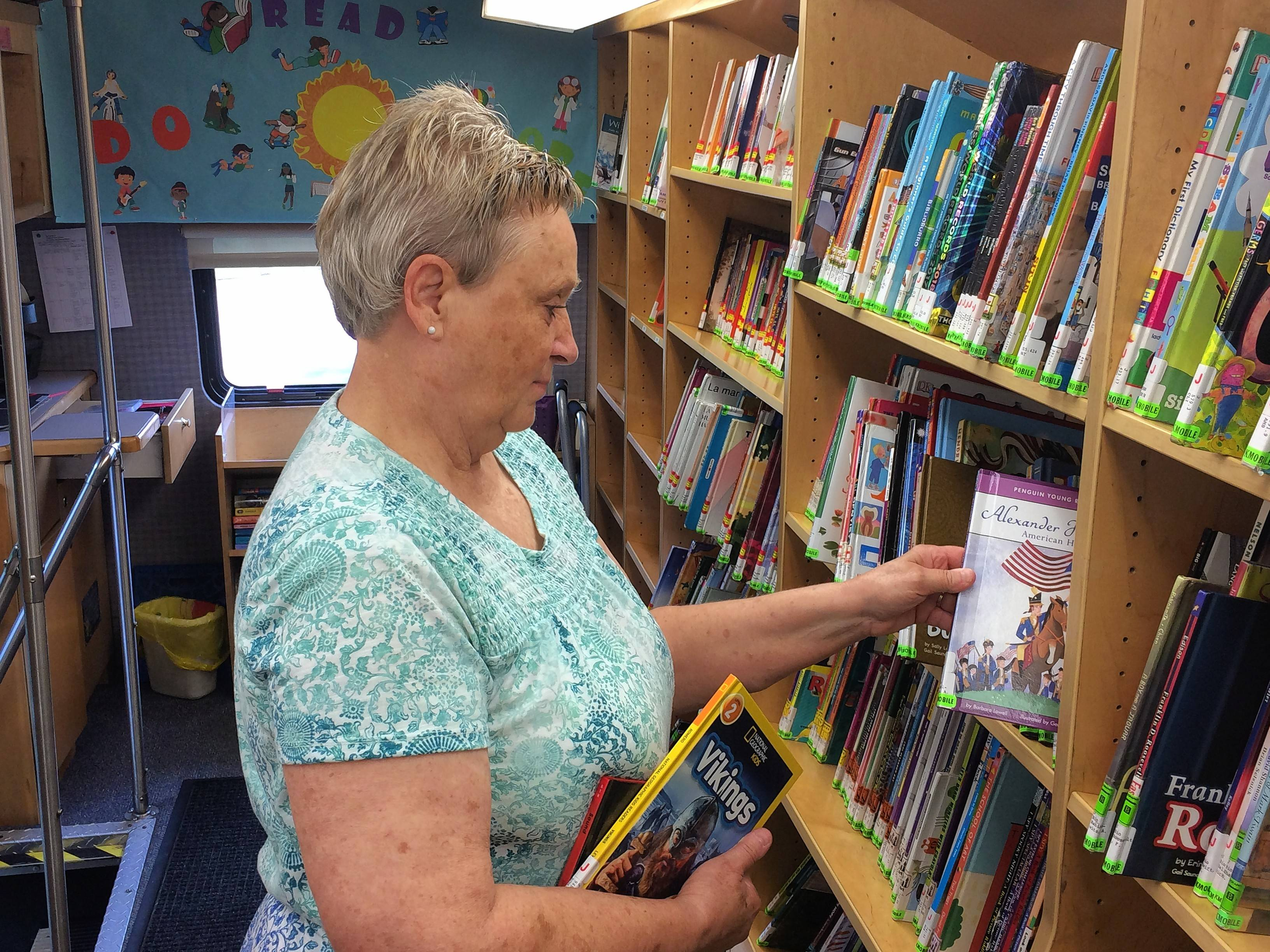 Bookmobile associate Linda Weagley shelves a book inside the Cook Memorial Public Library District's bookmobile.